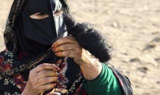Una donna omanita in vesti tradizionali mentre fila la lana