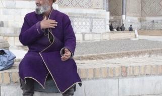Usi e costumi dell'Uzbekistan: uomo in piazza Registan con abiti della tradizione