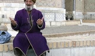 Un uomo ritratto con le vesti tradizionali nella piazza pubblica Registan a Samarcanda
